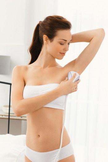 Lady using the iLight to treat her underarms.