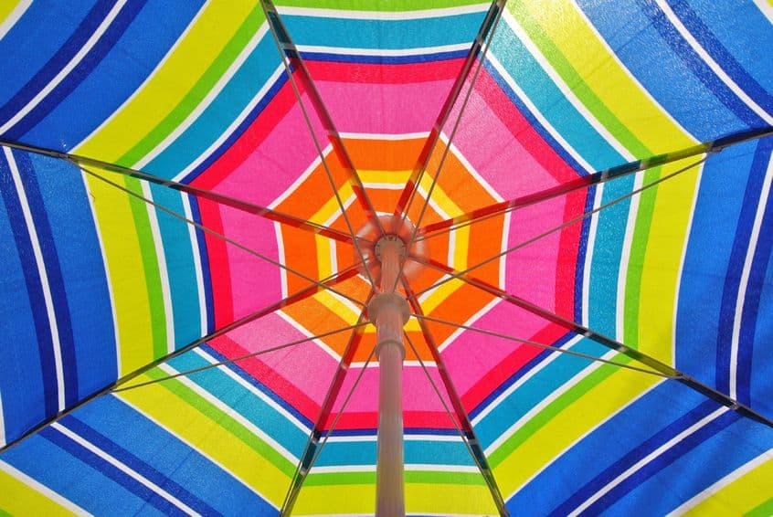the underside of a multi-coloured  open sun umbrella.
