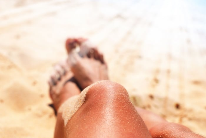 Ladies tanned legs relax on a beach and in the sunshine.