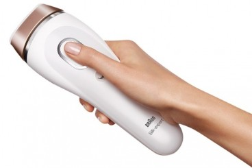 A hand holding the Braun Silk-expert IPL device and pressing the flash button with the thumb.