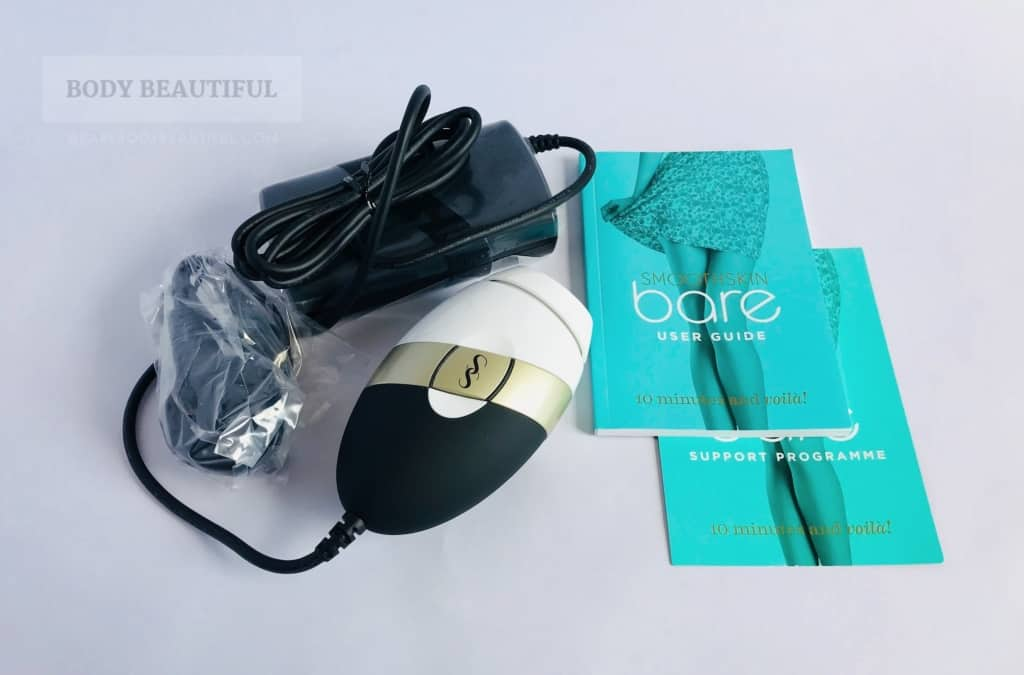 Photo of the box contents:  the compact Smoothskin Bare device and power pack, country specific power plug, user manual booklet and support programme card.