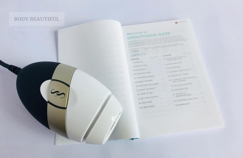 Photo of the user booklet open at the contents list next to the white, gold and black Bare.