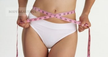 Photo of a lady's midriff wrapped with a pink tape measure showing shes very slim indeed.
