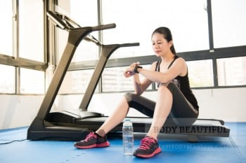 Photo of a lady in all the sports gear, but with no idea. She's sitting on the treadmill. Dumb ass.