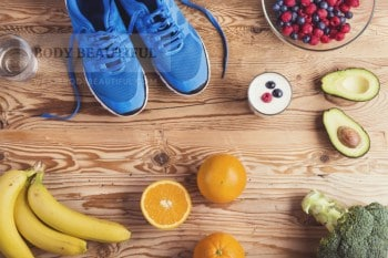 Photo depicting a healhty lifestyle with running shows, berries, yoghurt, avocado, broccoli, oranges and bananas. Not enough ale in this picture.