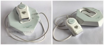 2 photos of the white and pastel blue Iluminage Touch. It's a compact base unit with hand held applicator attached on a flexible cord. The applicator sits in a cradle ontop of the base unit when not in use.