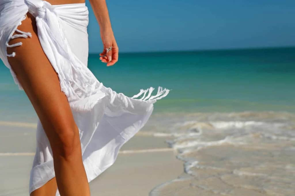 Photo of a ladies tanned legs in a white sarong on a sunny, white sandy beach with turquoise waters. Lush.