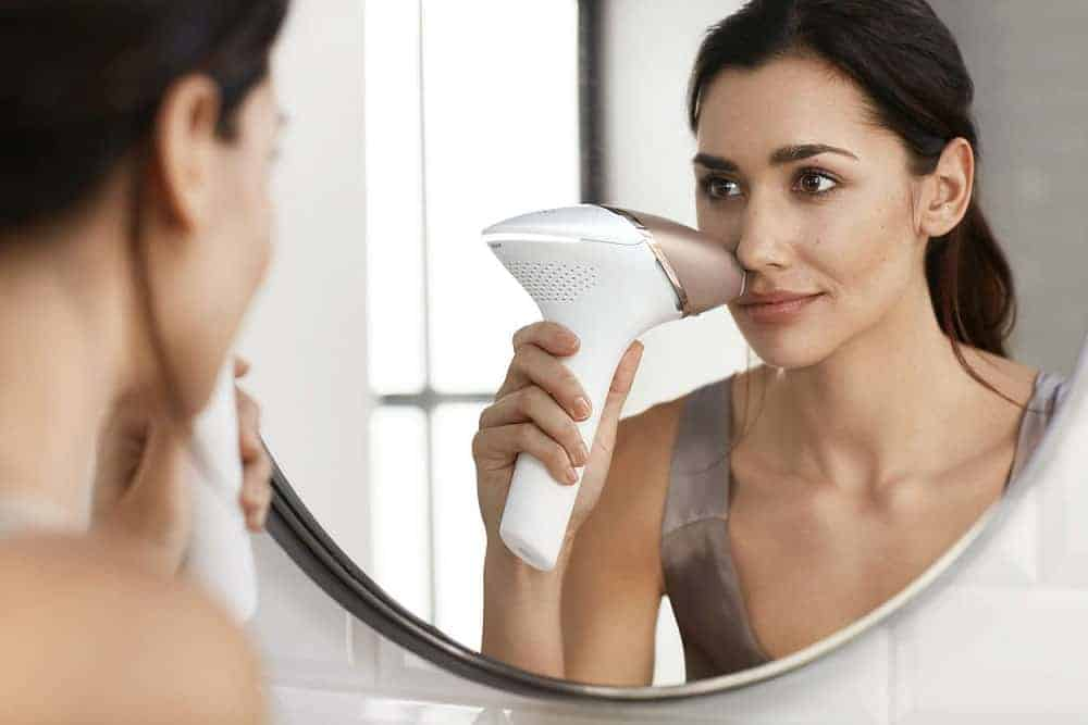 Photo of a lady looking in a mirror as she zaps her upper lip with the cordless Lumea Prestige.