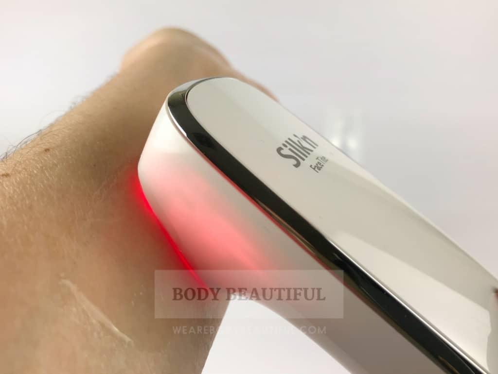 Photo of the FaceTite gliding across an arm nd glowing red