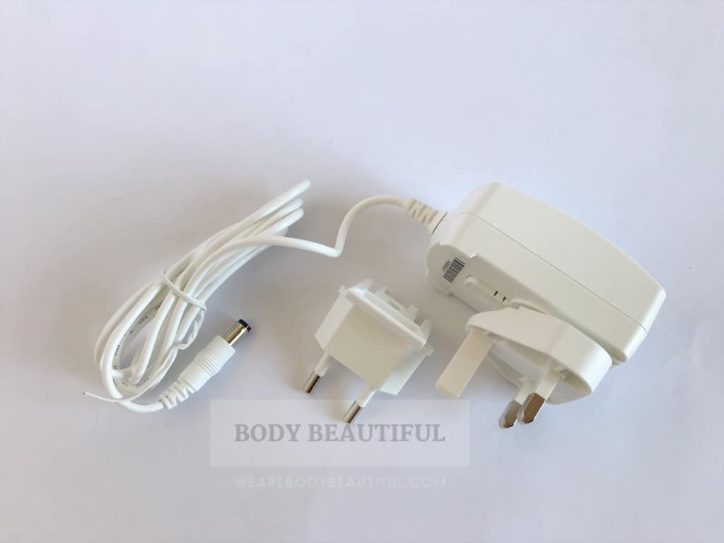Top-down photo of the white light-weight power cable with inter-changeable UK and European plug adaptor.