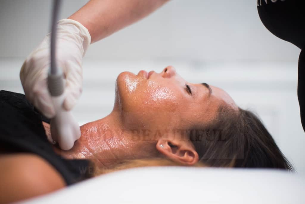 Radio Frequency skin tightening probe massaging skin on a lady's neck