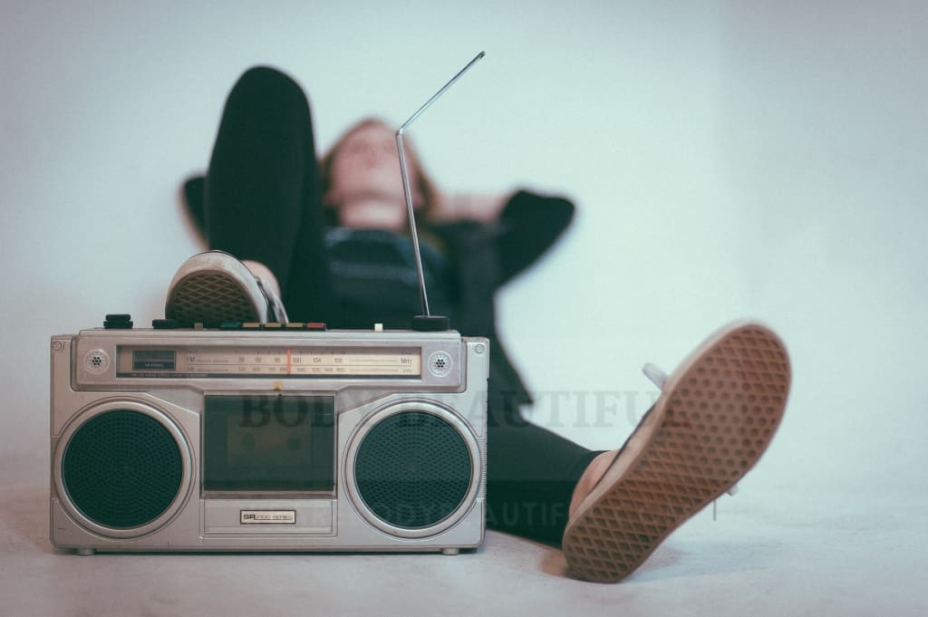 Person laying listening to an old school radio box.