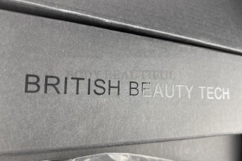 "Embossed 'Brtitish Beauty Tech"" on the top of the cardboard securing the power cable"