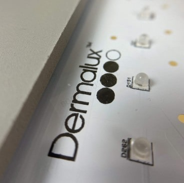 Close up photo of the Dermalux logo and LED bulbs on the Flex MD panel